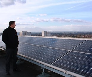 Northwards Home Improvements Manager Elliot Simm Looking Out At North Manchester Over Solar Panels On The Roof Of Northwards Somerton Court