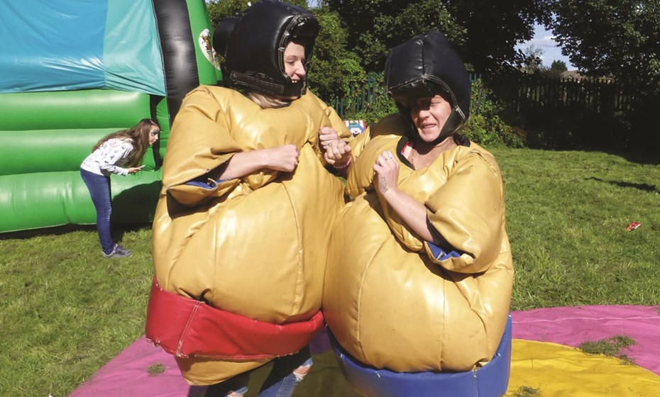 Two Residents Enjoying Fun In A Sumo Suit At One Of Our Fun Day Events